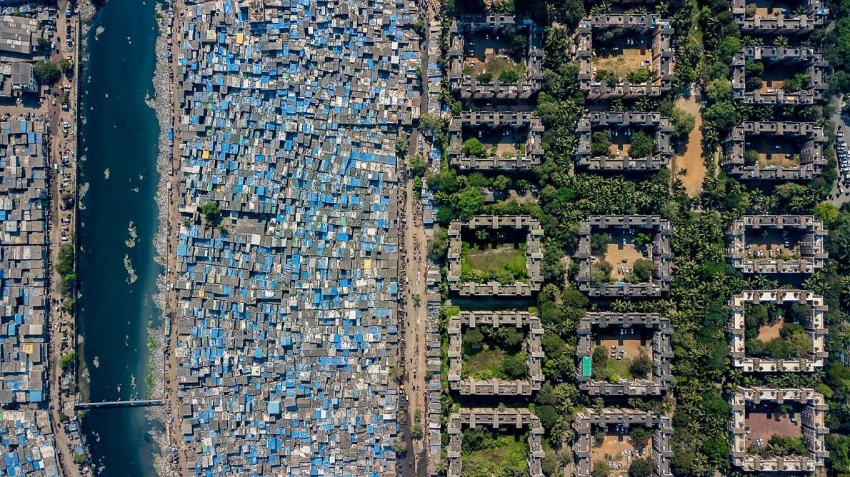 Un bidonville borde la rivière Mithi près de la bourse nationale de Bombay. La ville abrite à la fois un palace de 27 étages d'une valeur d'un milliard de dollars et le plus grand bidonville d'Asie. PHOTOGRAPHIE DE JOHNNY MILLER